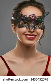 Half-turn shot of smiling lady with tied back dark hair, wearing red crop top. The girl is looking at camera, wearing iridescent masquerade mask with perforation. Vintage women's carnival accessory.