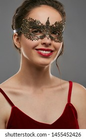 Half-turn shot of smiling woman with brunette hair, wearing wine red crop top. The young girl is looking at camera, wearing golden carnival mask with fancy perforation. Vintage carnival accessory.