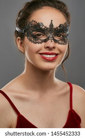 Half-turn shot of smiling woman with dark hair, wearing red crop top. The young girl is looking at camera, wearing silver carnival mask with fancy perforation. Vintage women's carnival accessory.