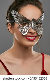 Half-turn shot of smiling woman with dark hair, wearing wine red crop top. The girl is looking at camera, wearing silver butterfly-shaped masquerade mask with perforation. Vintage carnival accessory.