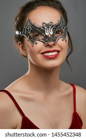Half-turn shot of smiling woman with dark hair, wearing wine red crop top. The young girl is raising her head, wearing silver bat-shaped carnival mask with perforation. Vintage carnival accessory.