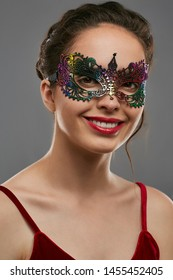 Half-turn shot of smiling woman with dark hair, wearing wine red crop top. The young girl is looking at camera, wearing iridescent carnival mask with fancy perforation. Vintage carnival accessory.