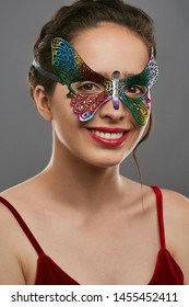 Half-turn shot of smiling woman with dark hair, wearing red crop top. The girl is looking at camera, wearing iridescent butterfly-shaped masquerade mask with perforation. Vintage carnival accessory.