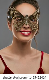 Half-turn shot of smiling woman with dark hair, wearing wine red crop top. The girl is looking at camera, wearing golden butterfly-shaped masquerade mask with perforation. Vintage carnival accessory.