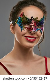 Half-turn shot of smiling woman with dark hair, wearing wine red crop top. The girl is looking at camera, wearing iridescent bat-shaped carnival mask with perforation. Vintage carnival accessory.