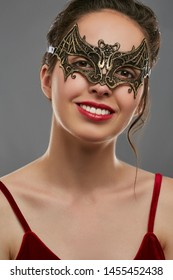 Half-turn shot of smiling woman with dark hair, wearing wine red crop top. The young girl is tilting her head, wearing golden bat-shaped carnival mask with perforation. Vintage carnival accessory.