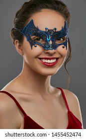 Half-turn shot of smiling woman with dark hair, wearing wine red crop top. The young girl is looking at camera, wearing blue bat-shaped carnival mask with perforation. Vintage carnival accessory.