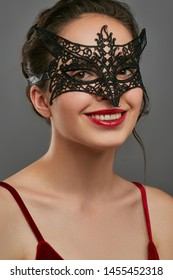 Half-turn shot of smiling woman with tied back dark hair, wearing wine red crop top. The lady is looking at camera, wearing black masquerade mask with fancy perforation. Vintage carnival accessory.