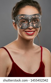 Half-turn shot of smiling woman with tied dark hair, wearing wine red crop top. The young girl is looking at camera, wearing silver carnival mask with fancy perforation, adorned with ladder braid.