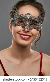 Half-turn shot of smiling woman with tied back dark hair, wearing wine red crop top. The girl is tilting her head, wearing silver masquerade mask with perforation. Vintage women's carnival accessory.