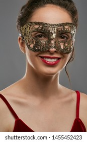 Half-turn shot of smiling woman with tied dark hair, wearing wine red crop top. The young girl is tilting her head, wearing golden carnival mask with fancy perforation, adorned with ladder braid.