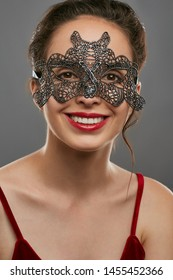Half-turn shot of smiling young woman with tied back dark hair, wearing wine red crop top. The girl is looking at camera, wearing silver masquerade mask with perforation. Vintage carnival accessory.