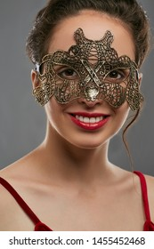 Half-turn shot of smiling young woman with tied back dark hair, wearing wine red crop top. The girl is looking at camera, wearing golden masquerade mask with perforation. Vintage carnival accessory.