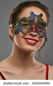 Half-turn shot of smiling young woman with tied back dark hair, wearing wine red crop top. The girl is raising head, wearing iridescent masquerade mask with perforation. Vintage carnival accessory.