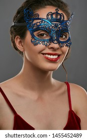 Half-turn shot of woman with dark hair, wearing wine red crop top. The smiling girl is looking at the camera, wearing blue asymmetric carnival mask with perforation in the view of crown on forehead.