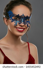 Half-turn shot of woman with dark hair, wearing wine red crop top. The smiling girl is looking at the camera, wearing blue asymmetric masquerade mask with perforation. Vintage theme party accessory.