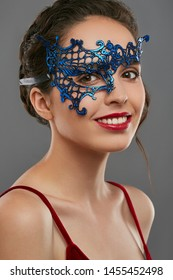 Half-turn shot of woman with dark hair, wearing wine red crop top. The smiling girl is looking at camera, wearing blue asymmetric carnival mask with perforation. Vintage women's carnival accessory.