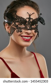 Half-turn shot of woman with tied back dark hair, wearing wine red crop top. The smiling lady is tilting her head, wearing black masquerade mask with fancy perforation. Vintage carnival accessory.