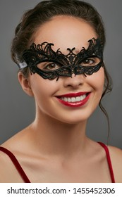 Half-turn shot of woman with tied back dark hair, wearing wine red crop top. The smiling lady is looking at camera, wearing black masquerade mask with fancy perforation. Vintage carnival accessory.