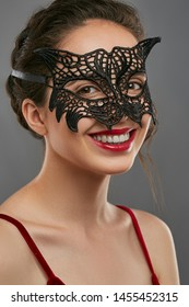Half-turn shot of woman with tied back dark hair, wearing wine red crop top. The laughing lady is looking at camera, wearing black masquerade mask with fancy perforation. Vintage carnival accessory.