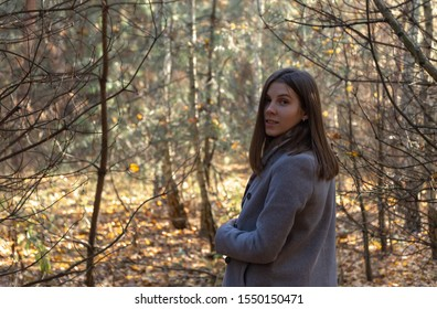 Half-turned girl in a gray coat, which stands in the forest on a sunny autumn day