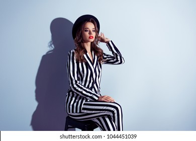 Half-turned portrait of graceful stunning exquisite posh self-assured famous popular wealthy luxurious classy lady diva with long curly hair dressed in catchy clothes isolated on gray background