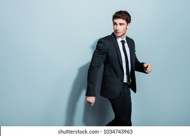 Half-turned portrait of handsome busy confident attractive serious minded thoughtful stunning entrepreneur going somewhere gesturing with hands looking to the back isolated gray background copy-space