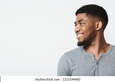 Half-turned smiling african-american man looking at copy space, white studio background