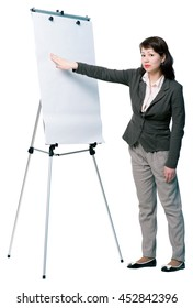 Half-turned young woman pointing at flip chart. Looking at the camera. Full length portrait isolated on white background.