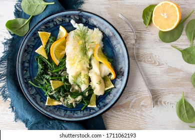 halibut fillet with spinach garnish and orange sauce on a blue ceramic plate on a light wooden table