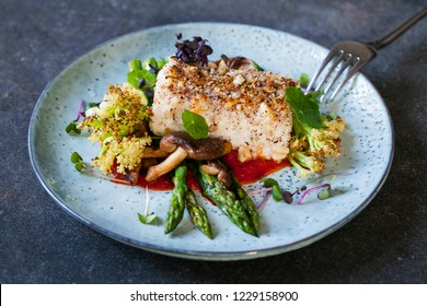 Halibut with hazelnut crust with roast red pepper sauce, asparagus, cauliflower and shiitake mushrooms