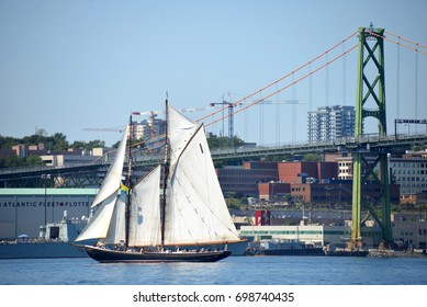 HALIFAX, CANADA - AUG 1, 2017: The iconic Bluenose II during the Tall Ships Parade of Sail in Halifax Harbour near the Macdonald Bridge and naval base. The original is featured on the Canadian dime.