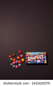 Halifax, Canada- May 31, 2019: Package of Smarties chocolate coated candy against a black background