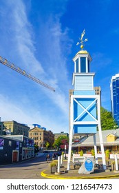 Halifax, Canada - September 23, 2018: The Dockyard clock, and other buildings, with locals and visitors, in Halifax harbor, Nova Scotia, Canada