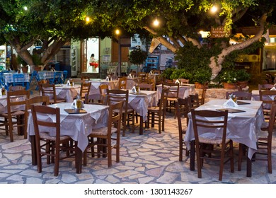 HALKI ISLAND, GREECE - AUGUST 27, 2018: Traditional greek restaurants, tables and chairs waiting for customers in the night. Halki is the smallest inhabited island of the Dodecanese, near Rhodes
