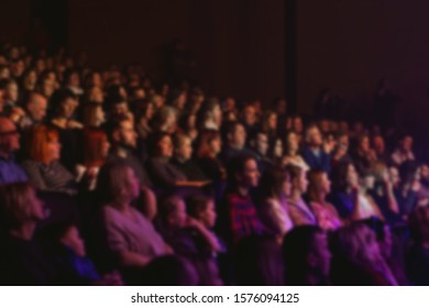 Сoncert hall, cinema, theater. People are sitting in the hall. Watching a movie. Abstract blurred image