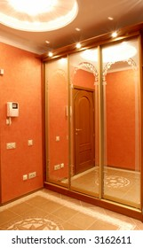hall designed in orange colour, wadrobe with a mirror, perfect illumination, lamp on the ceiling is placed in a big rosette