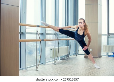 in the hall girl doing stretching near Barre.