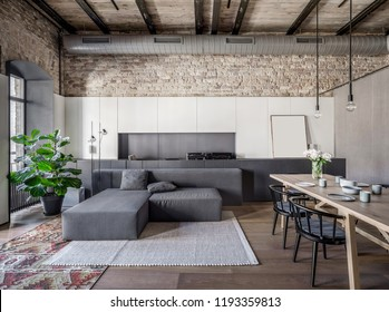 Hall in a loft style with brick walls, wooden ceiling and a parquet with a carpet on the floor. There is a gray sofa with pillows, wooden table with dishes, dark chairs, window, green plant, lamps.