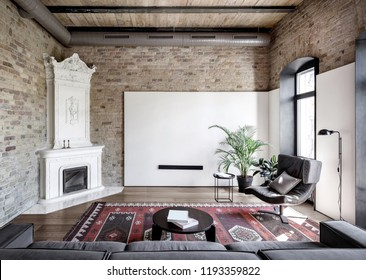 Hall in a loft style with brick walls, wooden ceiling and a parquet with a carpet on the floor. There is a gray sofa, round table with books, stand, armchair, white fancy fireplace, plants, windows.