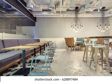 Hall in a loft style in a cafe with light walls and black and white tiles on the floor. There are sofas, different chairs, armchairs, round and square tables, hanging glowing lamps. Horizontal.