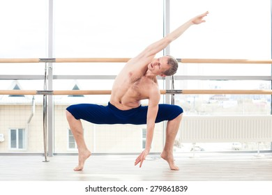 in the hall man doing stretching near Barre.