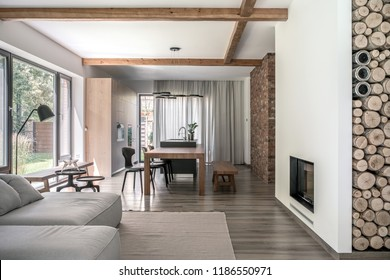 Hall in modern style with different walls and wooden beams on the ceiling. There is a table, chairs, benches, kitchen island, sofa, metal stands, floor lamp, fancy chandelier, fireplace with firewood.