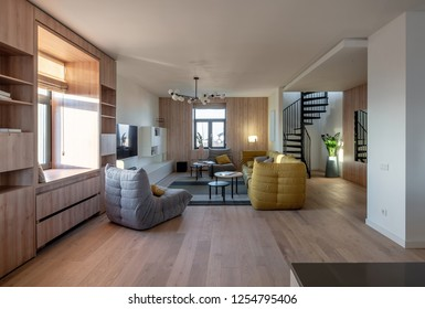 Hall in a modern style with light walls and a parquet with a carpet. There is a wooden bookcase, windows, gray armchairs, yellow sofa, pillows, lamps, TV, round tables, spiral staircase, green plants.