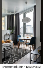 Hall in a modern style with white walls, parquet and dark textured carpet. There is a gray sofa with colorful pillows and plaid, glass and wooden tables, black stands, mirror, chairs, wicker lamp.