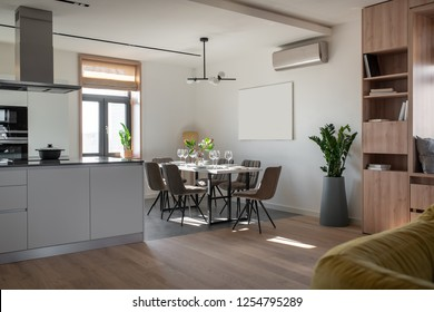 Hall in a modern style with white walls, parquet and tiles on the floor, kitchen zone. There is wooden bookcase, window with roman curtains, table with dishes, chairs, green plants, conditioner.