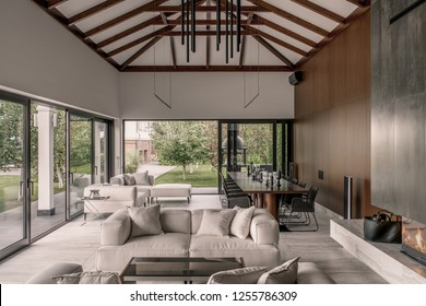 Hall in a modern style with white and wooden walls, large windows with glass doors, beams on a ceiling and a tiled floor. There is a burning fireplace, sofas with pillows, tables with wicker chairs.