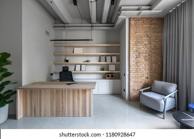 Hall in an office in a loft style with gray and brick walls. There is a wooden table, black chair, green plant in a big pot, round tables, light armchair, curtained window, hanging lamps, shelves.