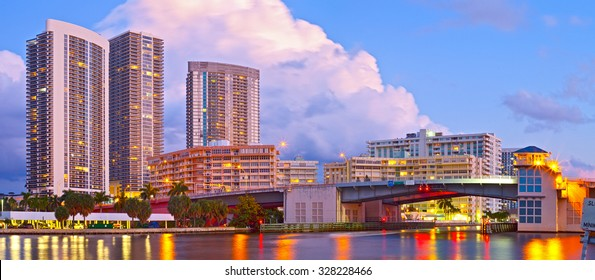 Hallandale Beach Florida, modern buildings and colorful illuminated bridge at sunset