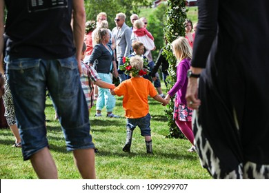 HALLESAKER, SWEDEN - JUNE 20, 2014: A young boy in orange t-shirt, rain boots and a flower crown is dancing around the maypole, celebrating midsummer. Seen from behind, holding hands with two kids.